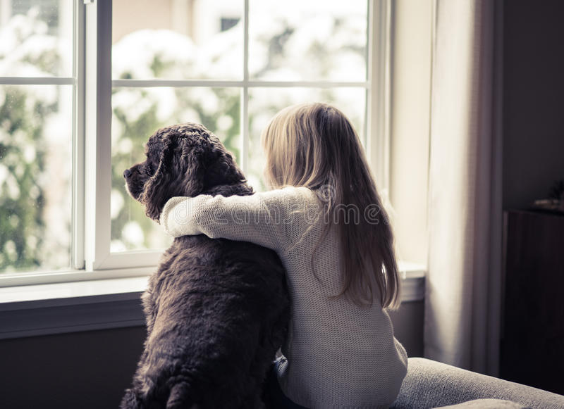 Kleines Mädchen und ihr Hund, die heraus das Fenster schaut. stockfotos
