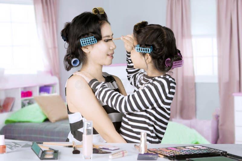 Kleines Mädchen und ihre Mutter, die mit Wimperntusche spielt stockbild
