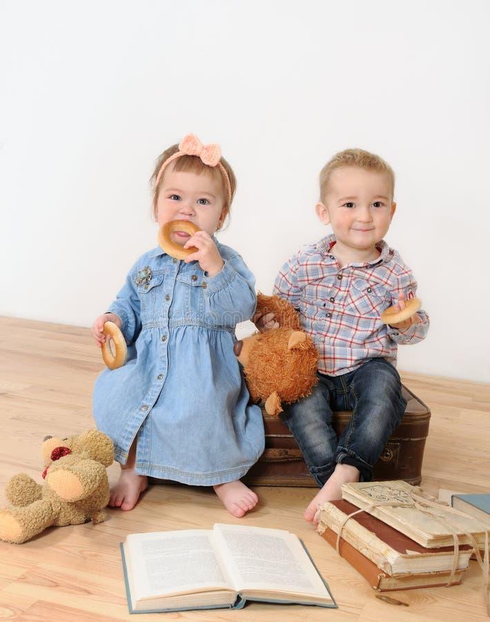 Kleines Mädchen und Junge, die auf Koffer nahe Buch sitzt stockfotos
