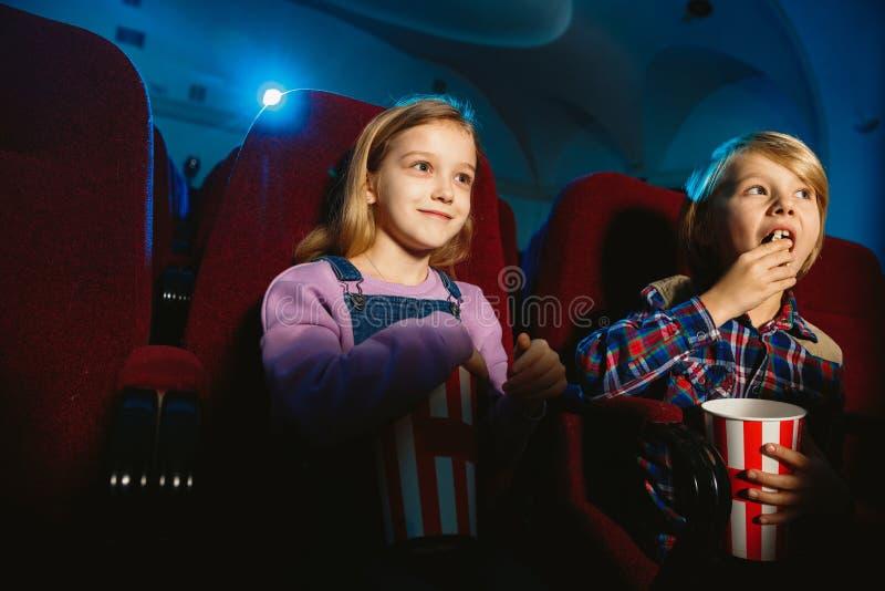 Kleines Mädchen und Junge, die einen Film in einem Kino ansehen lizenzfreies stockbild