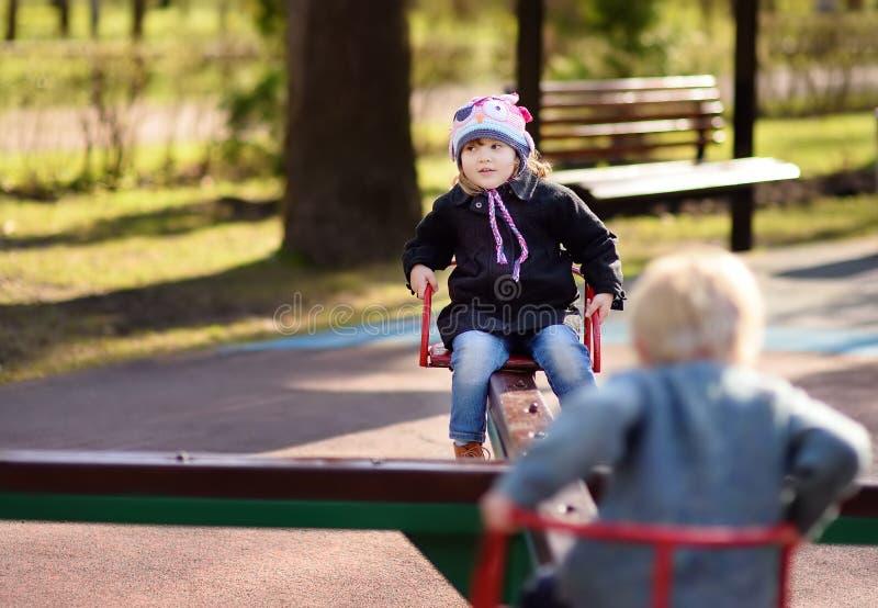 Kleines Mädchen und Junge, die Spaß mit Karussell auf Spielplatz im Freien hat lizenzfreies stockfoto
