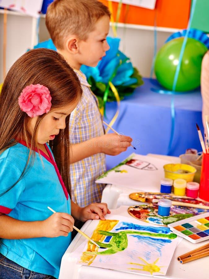 Kleines Mädchen und Junge mit Bürstenmalerei im Kindergarten stockfotografie