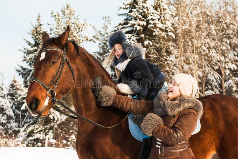 Kleines Mädchen und Mutter nahe Pferd in einem Winter stockfotos