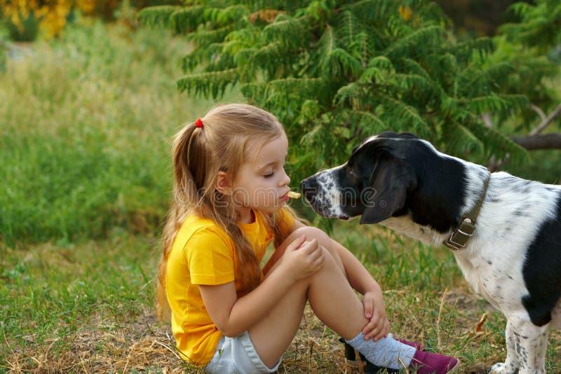 Kleines Mädchen und nicht reinrassiger Hund draußen stockbild