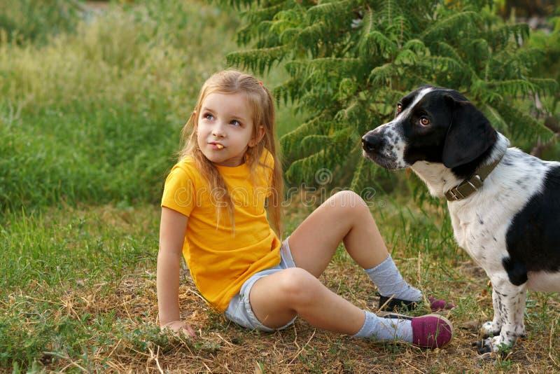 Kleines Mädchen und nicht reinrassiger Hund draußen lizenzfreie stockbilder