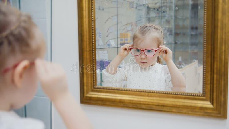 Kleines Mädchen versucht neue Gläser nahe Spiegel - Einkaufen in der Augenheilkundeklinik lizenzfreies stockfoto