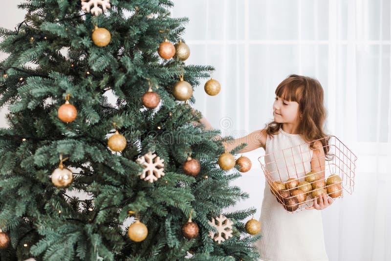 Kleines Mädchen verziert enormen grünen Weihnachtsbaum lizenzfreie stockfotografie