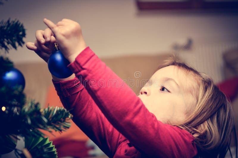 Kleines Mädchen verziert Weihnachtsbaum im Retro- Filtereffekt stockfoto