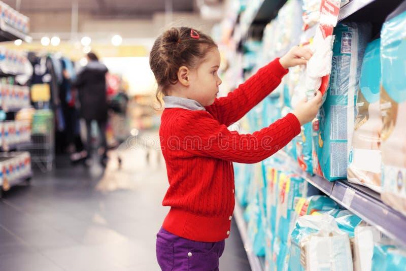 Kleines Mädchen wählt Windeln im Supermarkt vor stockfotografie