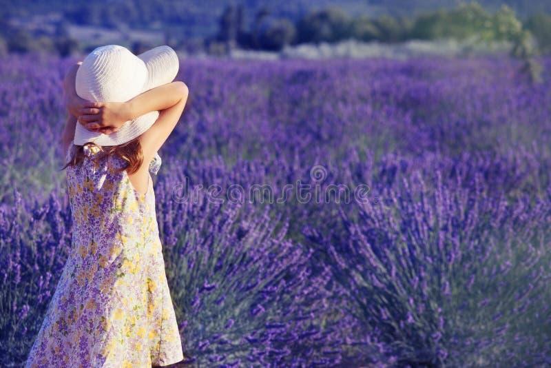 Kleines Mädchen, welches das Lavendelfeld betrachtet stockfotografie