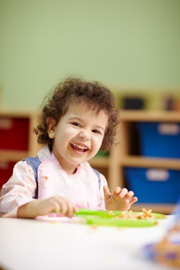 Kleines Mädchen, welches das Mittagessen im Kindergarten isst stockfoto