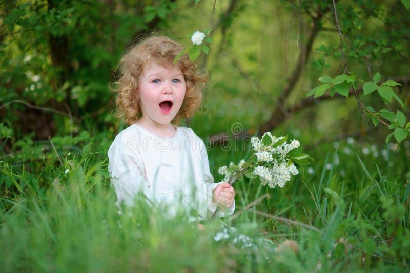 Kleines Mädchen, welches das stilvolle weiße Kleid sitzt im Gras trägt SU lizenzfreies stockfoto