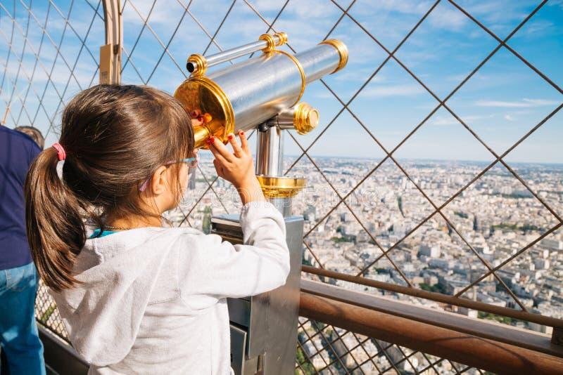 Kleines Mädchen, welches das Teleskop im Eiffelturm verwendet lizenzfreies stockbild