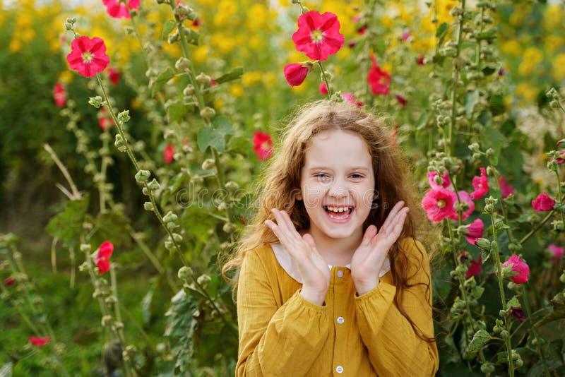 Kleines Mädchen, welches die glücklichen Augen oben anheben ihre Hände und Shows whi hat stockfoto