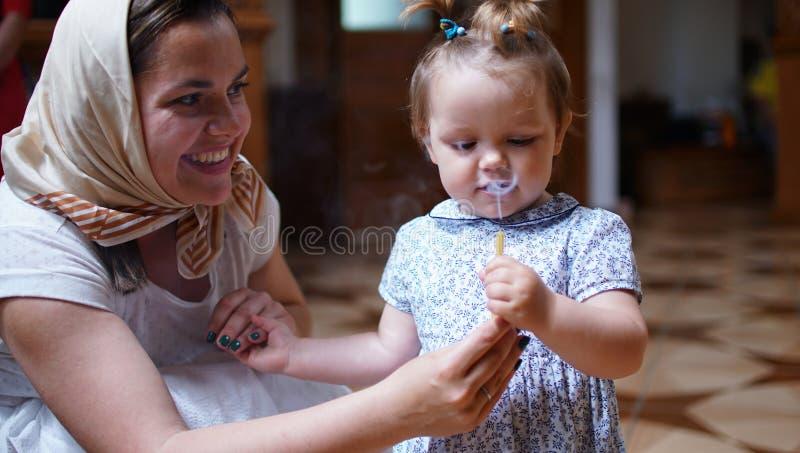 Kleines Mädchen, welches die Kerze in der orthodoxen Kirche, ersten Besuch zum aChurch hält stockbilder