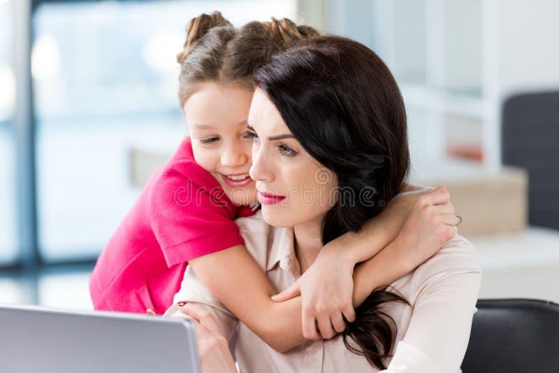 Kleines Mädchen, welches die Mutter arbeitet mit Laptop umarmt lizenzfreie stockfotos