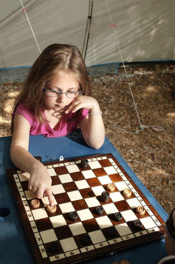 Kleines Mädchen, welches Kampieren des Entwurfsbrettes das im Freien im sunn spielt stockfotografie
