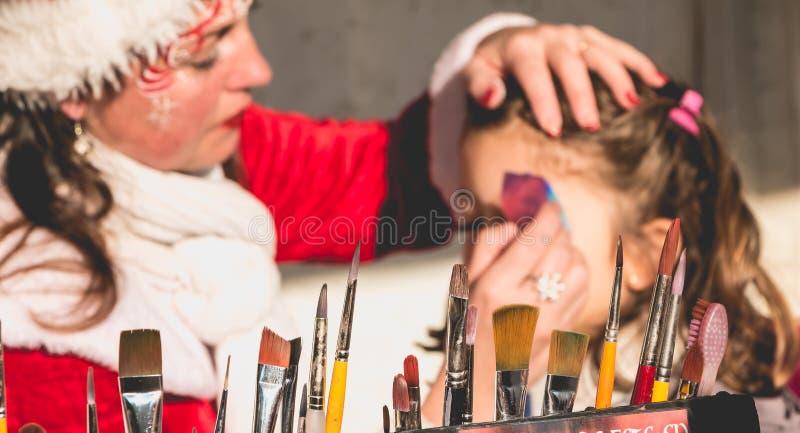 Kleines Mädchen wendet Make-up in einem Stand an stockfotos