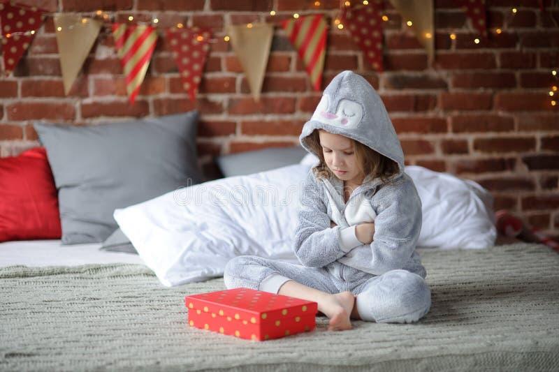 Kleines Mädchen wird durch das empfangene Geschenk enttäuscht stockbilder