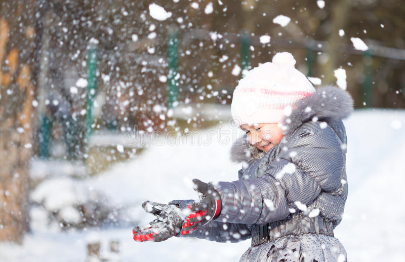 Kleines Mädchen wirft Schnee stockbild
