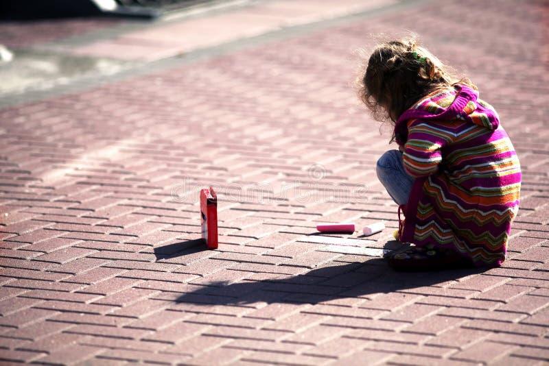 Kleines Mädchen zeichnet an der Straße lizenzfreie stockfotografie