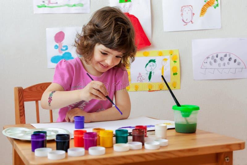 Kleines Mädchen zeichnet mit Farben und Malerpinsel lizenzfreies stockfoto