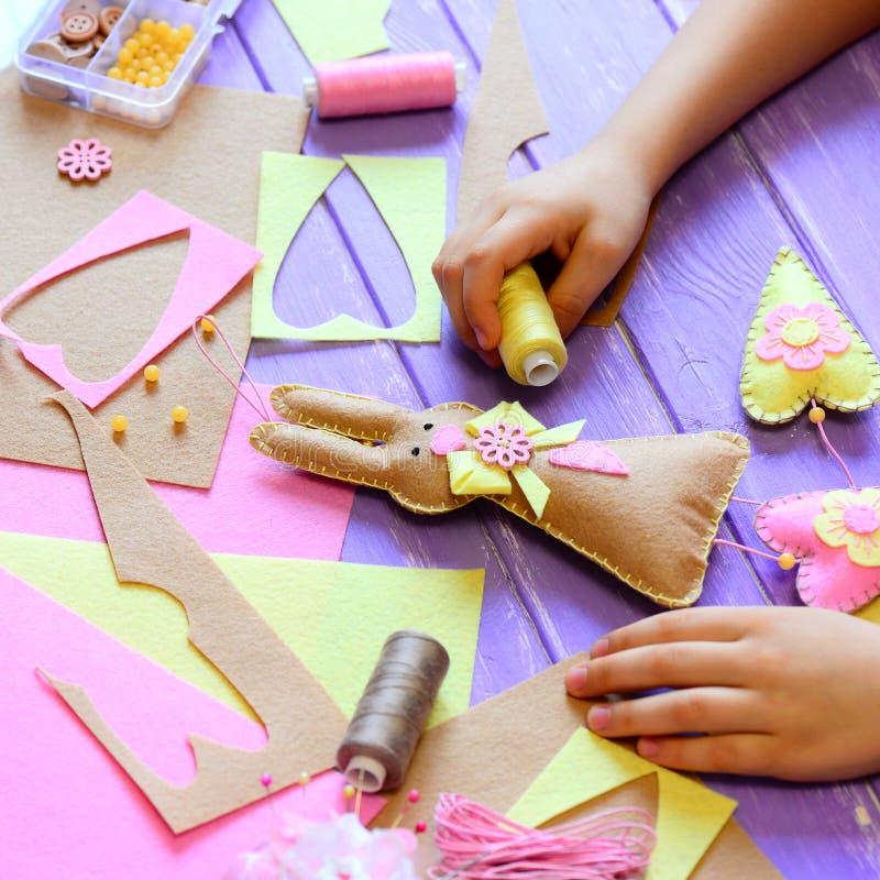 Kleines Mädchen zeigt ein Filzhäschen in den Händen Mädchen machte einen Filz nettes Häschen mit Herzen für Ostern Werkzeuge und  lizenzfreie stockfotografie