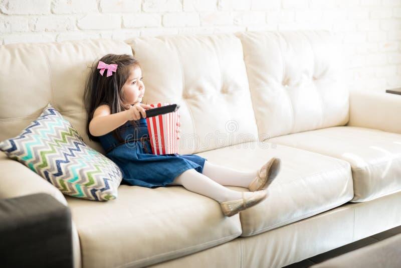 Kleines Mädchen zu Hause, das mit Popcorn fernsieht stockfotografie