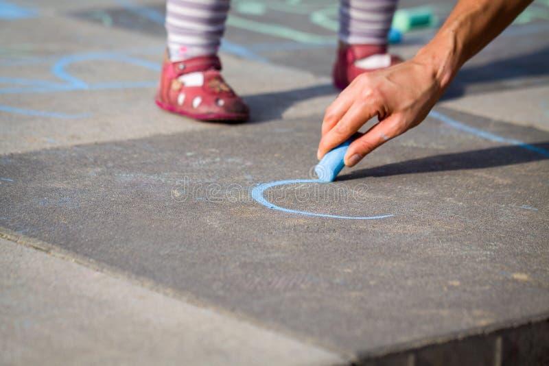 Kleines Mädchenbein und -mutter, die blaue Kreide zeichnet lizenzfreies stockbild