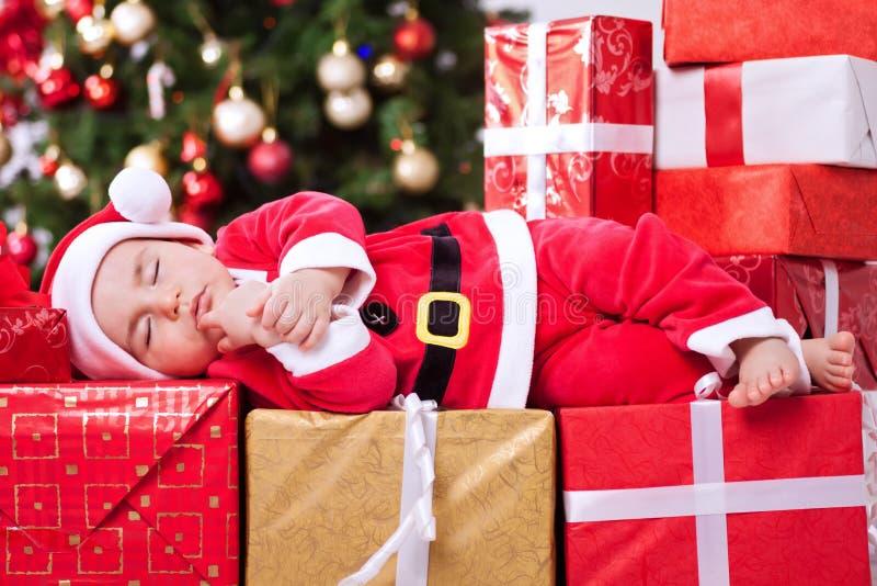 Kleines müdes Baby Sankt, die auf Geschenken für Weihnachten schläft lizenzfreie stockfotos