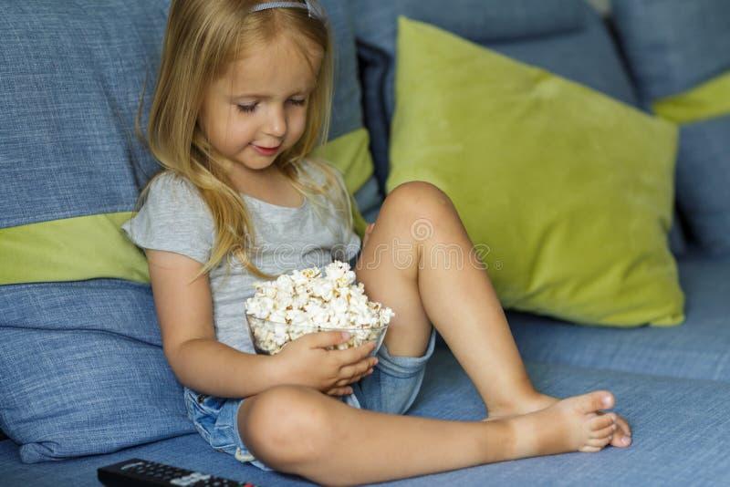 Kleines M?dchen, das Fernsieht Gl?ckliches nettes kleines M?dchen, das eine Sch?ssel mit Popcorn h?lt lizenzfreie stockfotografie