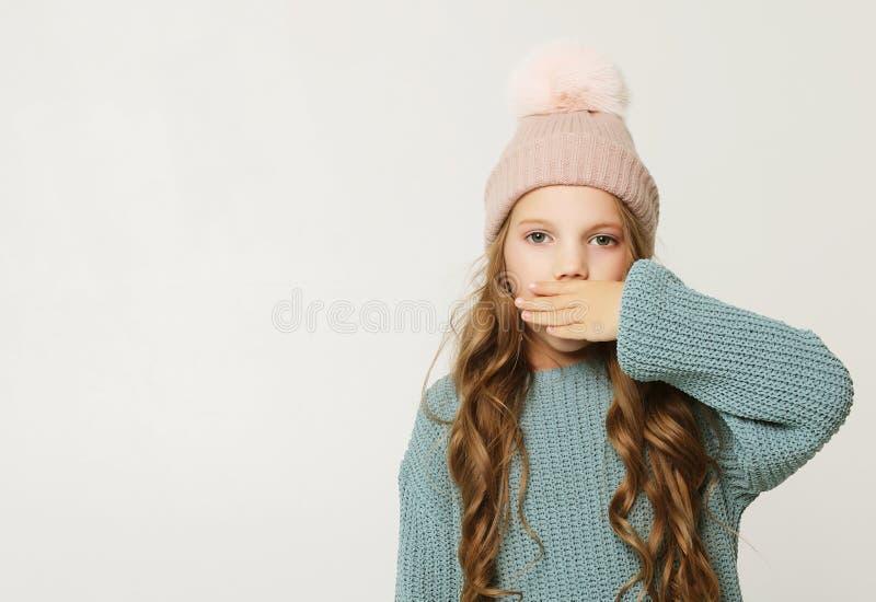 Kleines M?dchen, das ihren Mund mit ihrer Hand bedeckt Lebensstil und Kindheitskonzept stockfotografie
