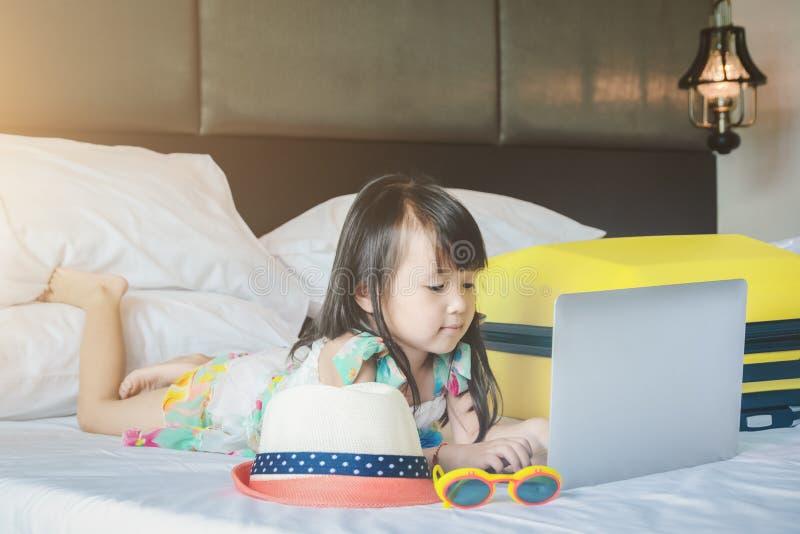 Kleines M?dchen, das mit Laptop auf dem gl?cklichen L?cheln des Betts unter Verwendung des Internets aufpasst und hat Spa? im Kin lizenzfreie stockbilder
