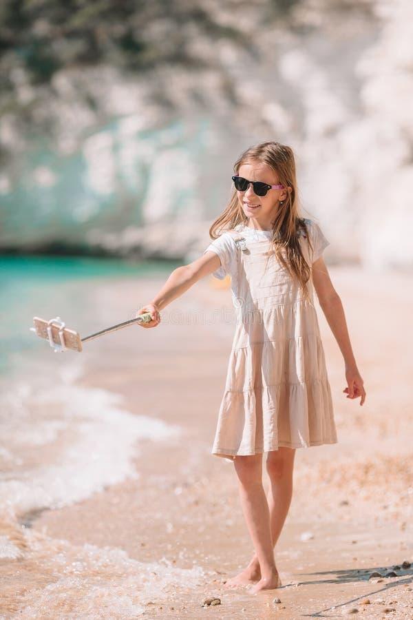 Kleines M?dchen, das selfie durch ihren Smartphone auf dem Strand nimmt stockbild