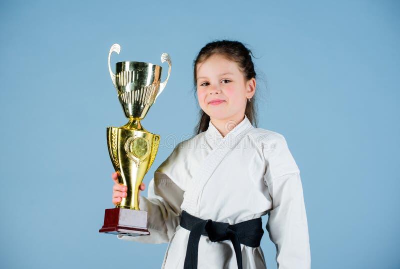 kleines M?dchen des Siegers in der Gisportkleidung ?bendes Kung Fu Gl?ckliche Kindheit Sporterfolg im Einzelkampf M?dchen mit lizenzfreie stockfotografie