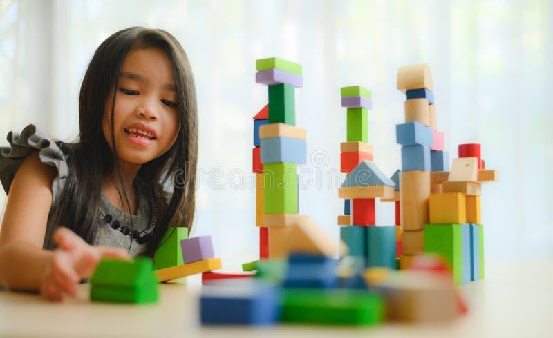 Kleines M?dchen in einem bunten Hemd, das mit den Baubaukl?tzen errichten einen Turm spielt Kinder mit Vorstand Kinder an der Tag stockfoto