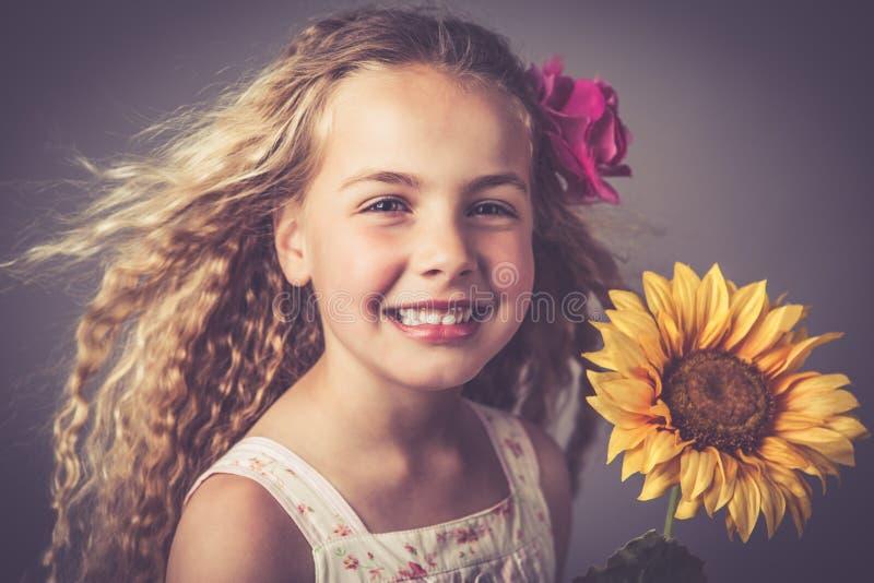 Kleines M?dchen mit einer Sonnenblume lizenzfreie stockfotografie