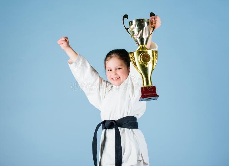 kleines M?dchen mit Meistercup chinesische KONGFU Kinder kleines M?dchen des Siegers in der Gisportkleidung ?bendes Kung Fu kindh stockfotos