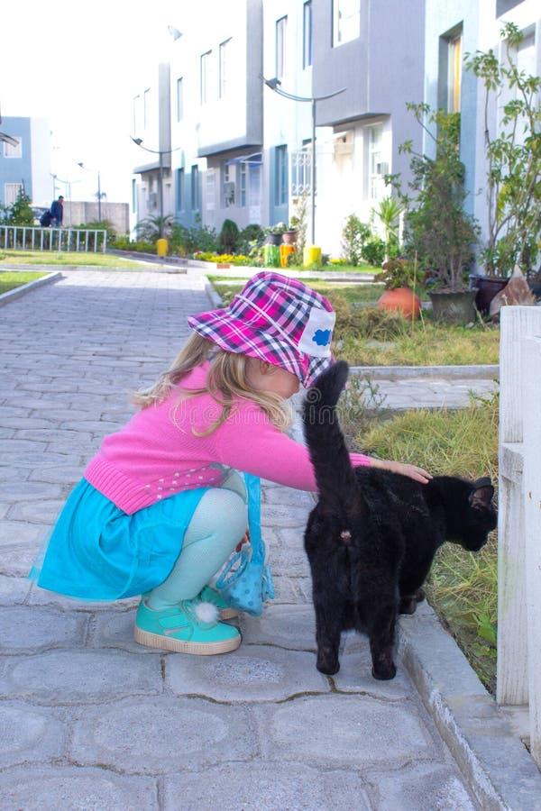 Kleines modernes Mädchen streichelt eine schwarze Katze auf der Straße Baum auf dem Gebiet lizenzfreie stockfotos