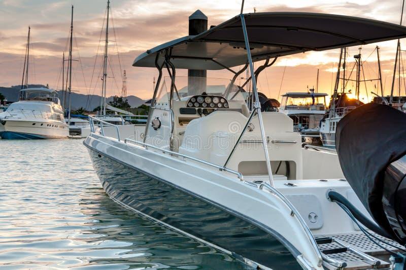 Kleines Motorbootankern am Jachthafen zur Sonnenuntergangzeit stockbilder