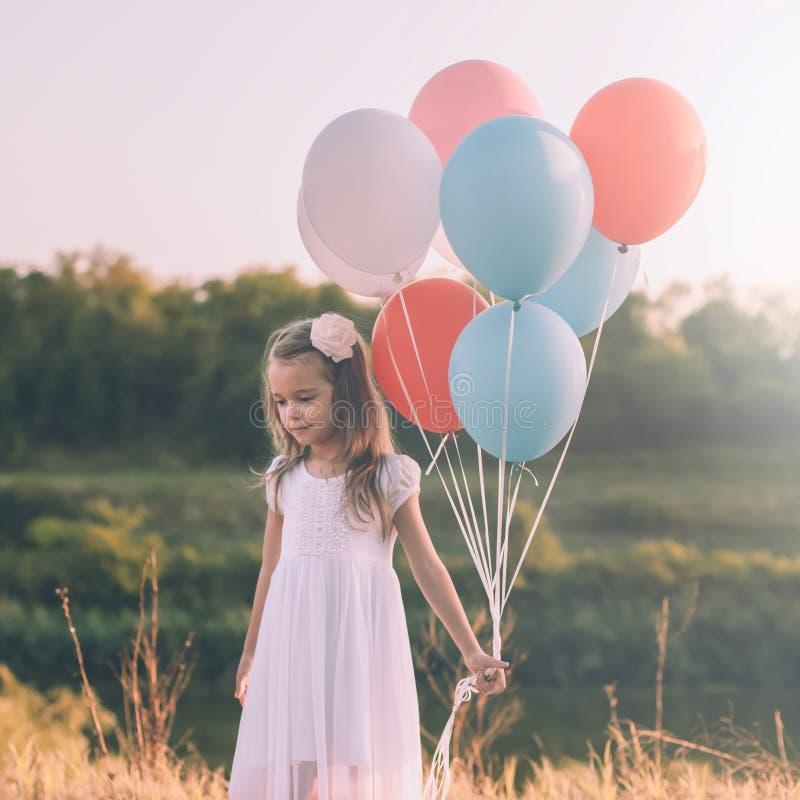 Kleines nachdenkliches Mädchen mit bunten Ballonen lizenzfreie stockfotografie