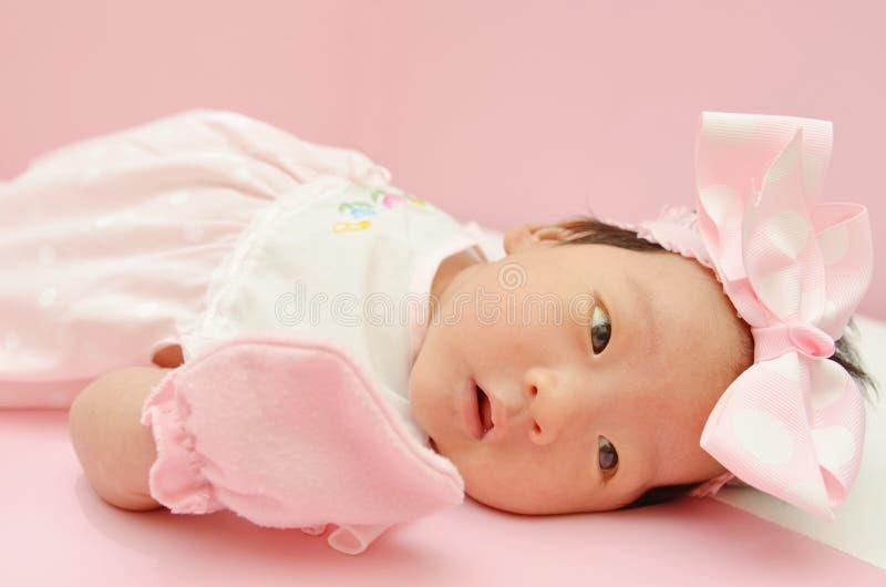 Kleines nettes asiatisches Mädchenbaby mit süßem Kleid und schönem Stirnband mit leerem copyspace stockfoto