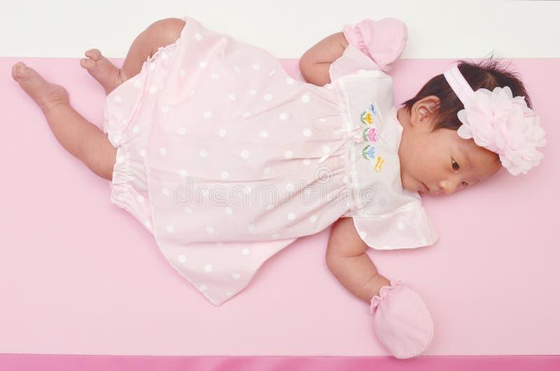 Kleines nettes asiatisches Mädchenbaby mit süßem Kleid und schönem Stirnband mit leerem copyspace stockfotografie