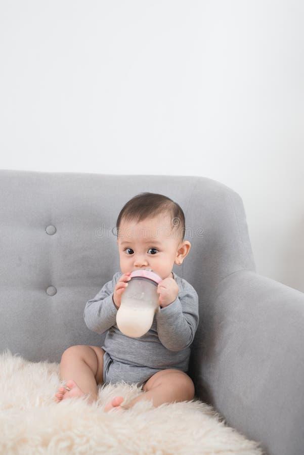 Kleines nettes Baby, das im Raum auf Trinkmilch des Sofas von der Flasche und vom L?cheln sitzt Gl?ckliches Kind Familienleute In lizenzfreies stockbild