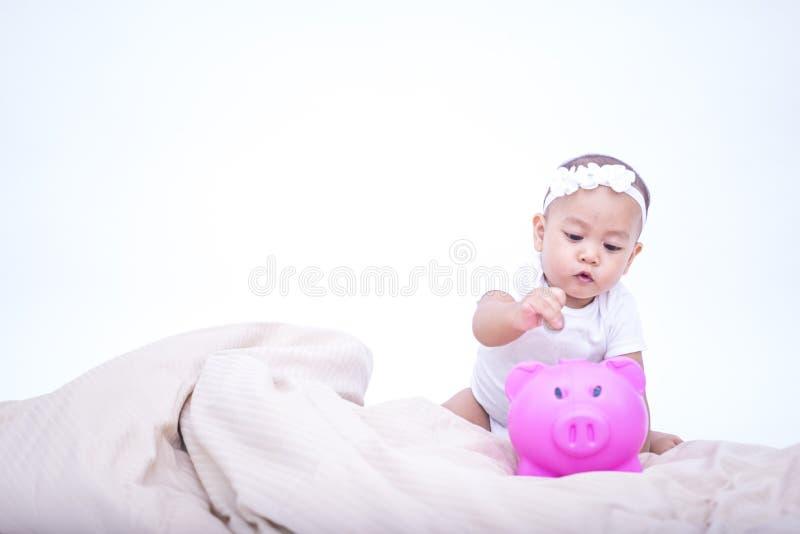 Kleines nettes Baby, das Münze in das Sparschwein einsetzt lizenzfreies stockbild