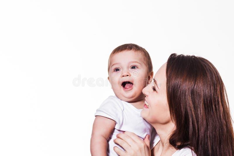 Kleines nettes Baby, das in Mutter ` s Hand lacht stockbild