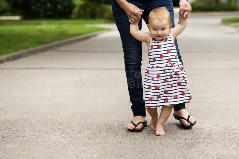 kleines nettes Baby, unternimmt seiner Mutter seine ersten Schritte und an hält stockfoto