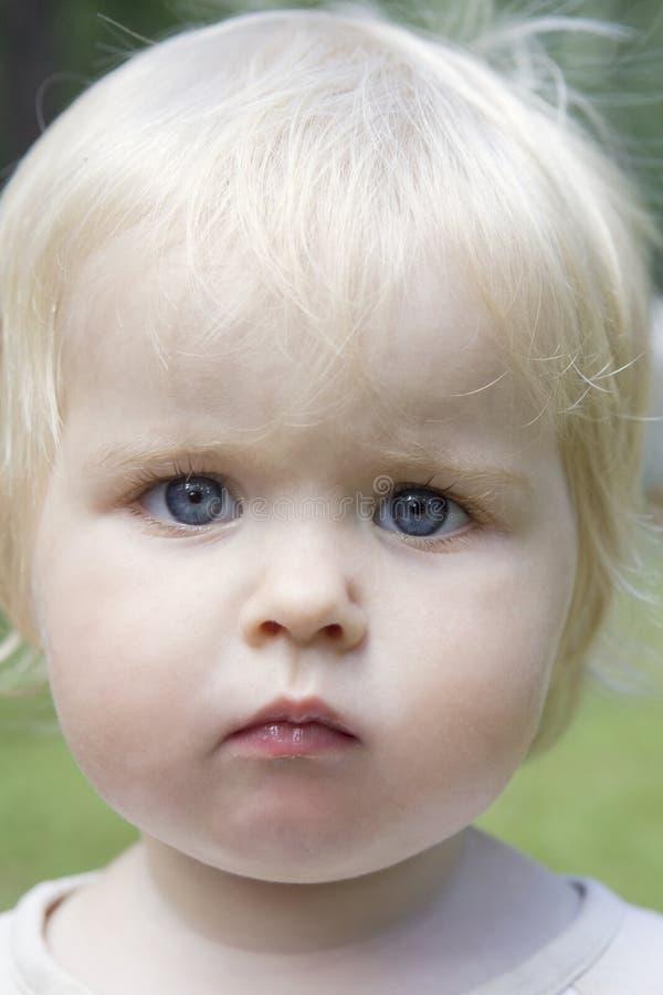 Kleines nettes blondes ernstes Baby stockfotos