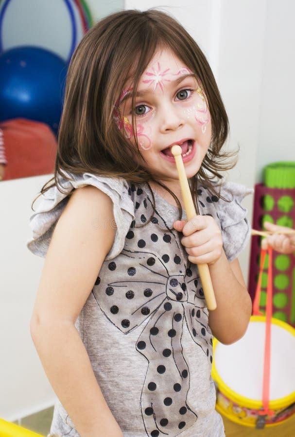 Kleines nettes Brunettemädchen, das emotionales mit zu Hause spielen aufwirft stockbilder