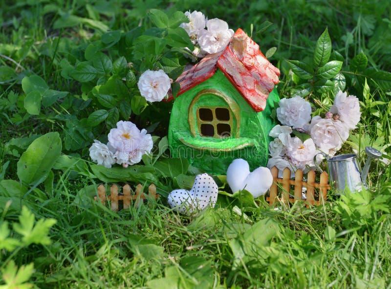 Kleines nettes grünes Haus mit Rosen, kleiner Zaun, Herzen und Gießkanne im Garten stockfotografie